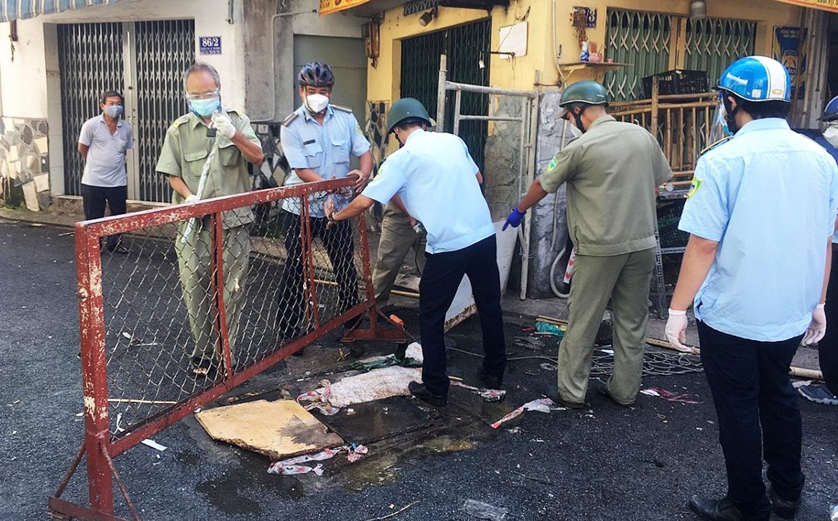 Bảo vệ dân phố cùng lực lượng trật tự đô thị tháo bỏ rào chắn tại con hẻm đường Âu Cơ, quân Tân Bình, trưa 27/9. Ảnh: Đăng Khôi