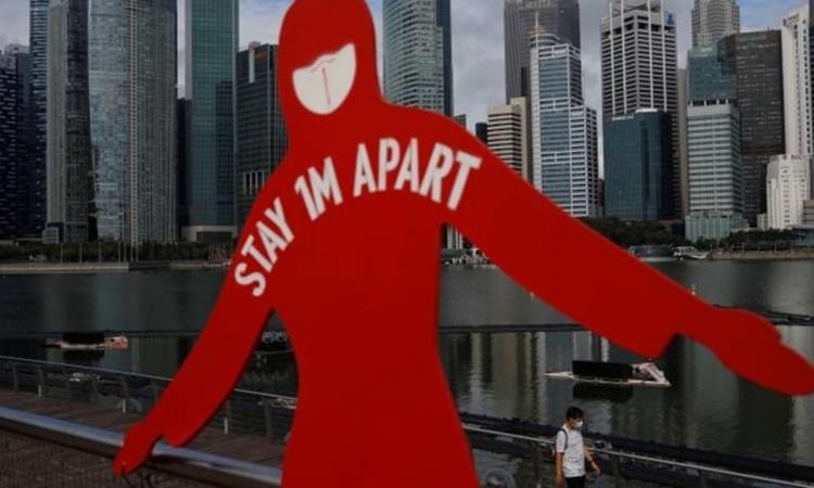 Tấm biển ghi thông điệp giữ khoảng cách một mét được dựng lên ở Vịnh Marina, Singapore, ngày 22/9. Ảnh: Reuters.