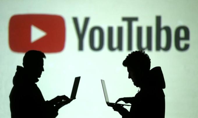 Hai người dùng máy tính trước logo của YouTube hồi tháng 3/2018. Ảnh: Reuters.