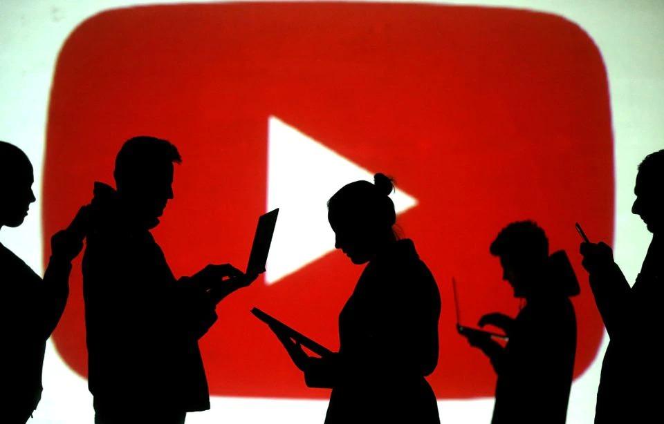 Bóng người dùng máy tính xách tay và thiết bị di động cạnh hình chiếu biểu tượng YouTube trong ảnh minh họa năm 2018. Ảnh: Reuters.