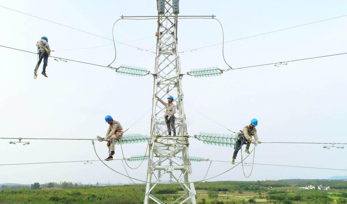 Công nhân điện lực sửa chữa đường dây ở Trung Quốc. Ảnh: AFP.