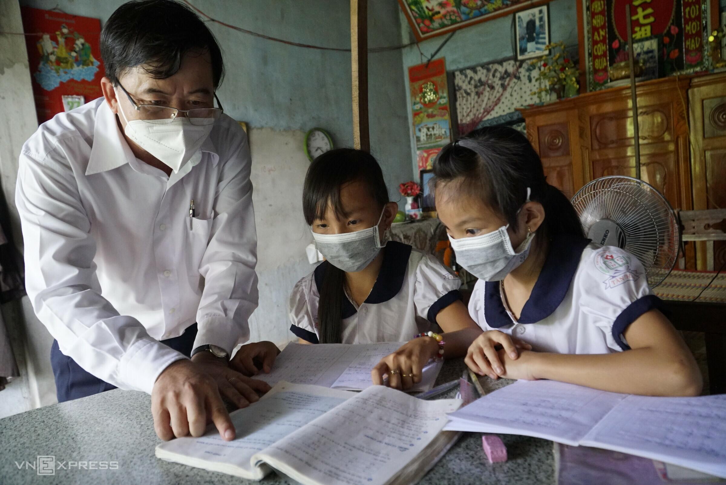 Khánh Băng và Tuyết Mai, học sinh Trường Tiểu học Tân Thạnh 1 chưa có thiết bị học trực tuyến nên được thầy giáo chỉ bài và giao bài tập để làm. Ảnh: Ngọc Tài