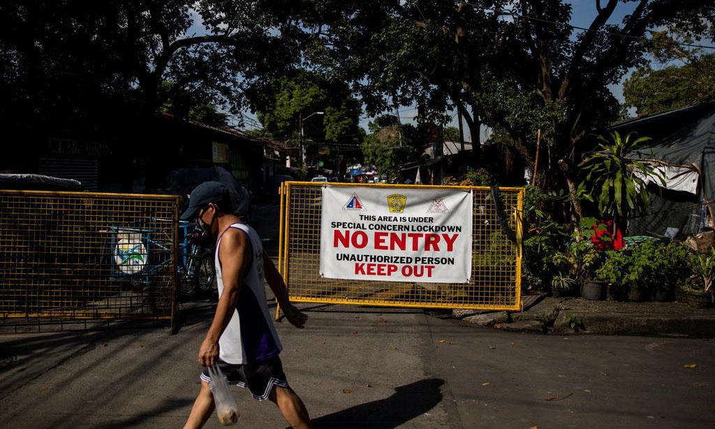 Người dân đi qua một con đường bị phong tỏa tại thành phố Quezon thuộc vùng đô thị Manila, Philippines, hôm 16/9. Ảnh: Reuters.