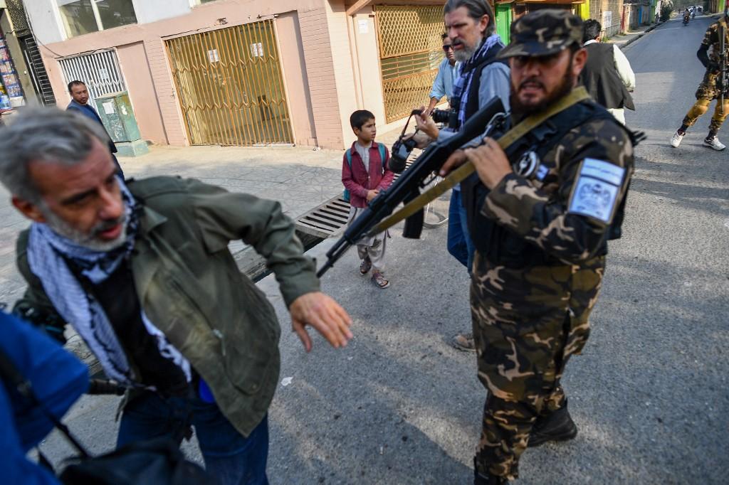 Một thành viên lực lược đặc nhiệm Taliban đẩy một nhà báo (trái) đang đưa tin về cuộc biểu tình của phụ nữ ngoài trường học ở Kabul hôm 30/9. Ảnh: AFP