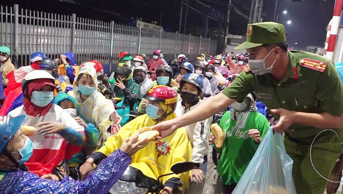 Dòng người về quê tập trung tại cửa ngõ tỉnh An Giang được phát thực phẩm chống đói. Ảnh: Tiến Tầm