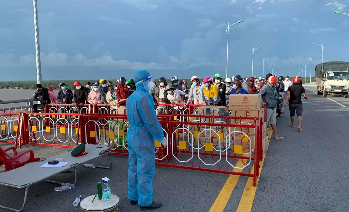 Người về Trà Vinh đang chờ tại chốt kiểm soát trên cầu Cổ Chiên trưa 2/10. Ảnh: Hoài Phong
