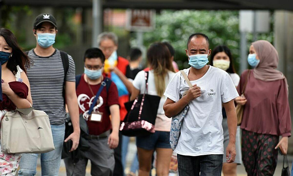 Dân Singapore đeo khẩu trang đi bộ trên phố ngày 14/5. Ảnh: Reuters