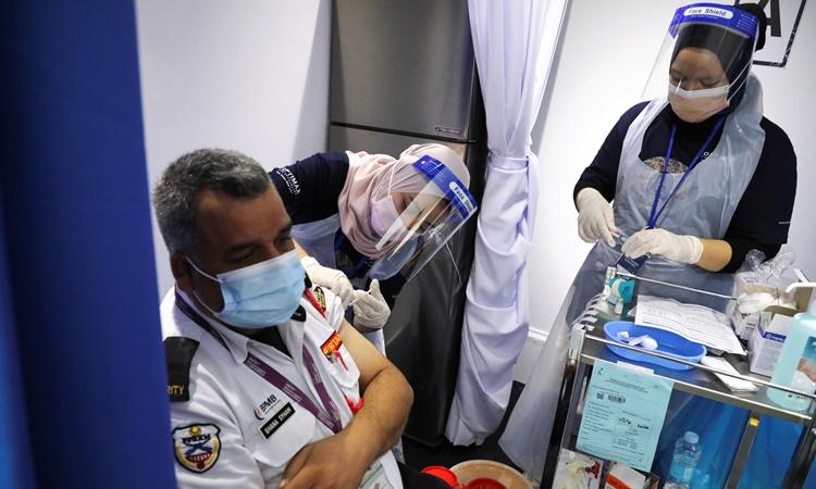 Nhân viên y tế tiêm vaccine Covid-19 cho một lao động nước ngoài ở thủ đô Kuala Lumpur, Malaysia, ngày 8/6. Ảnh: Reuters.