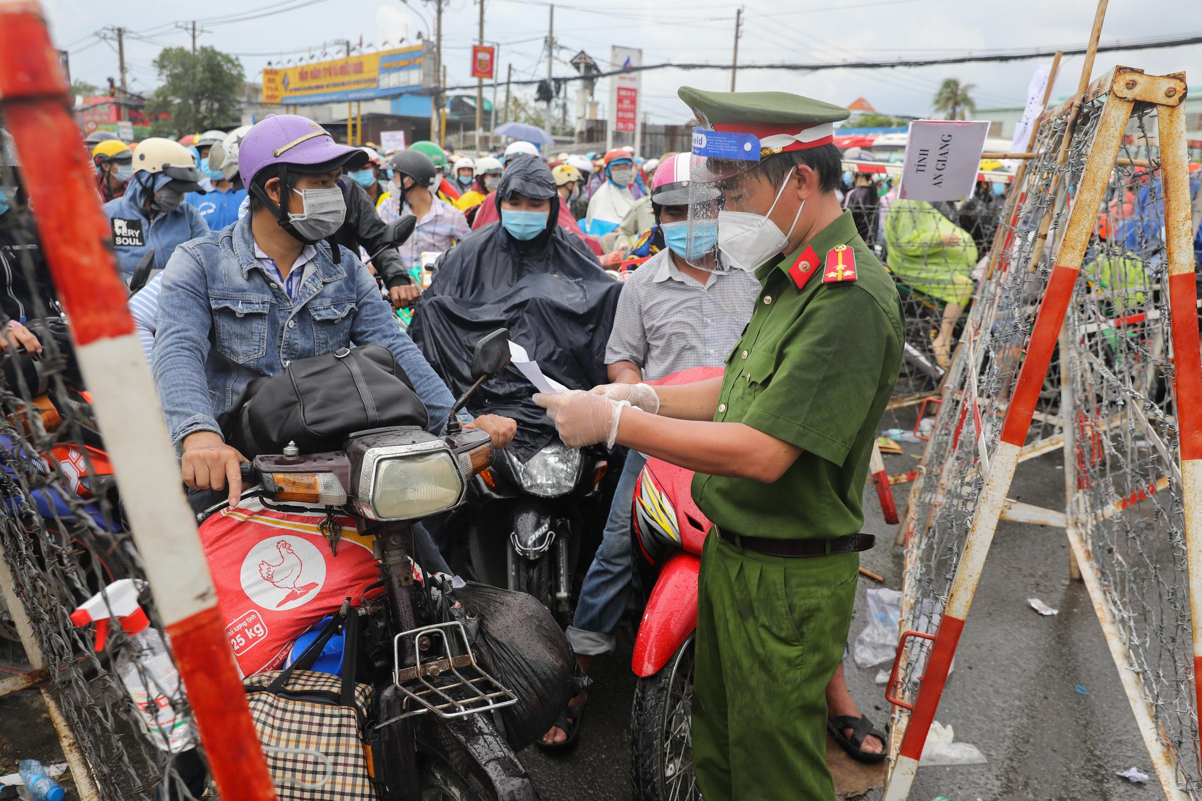 Người dân chờ ở chốt kiểm soát trên quốc lộ 1A, huyện Bình Chánh TP HCM để chờ về quê ngày 1/10. Ảnh: Quỳnh Trần