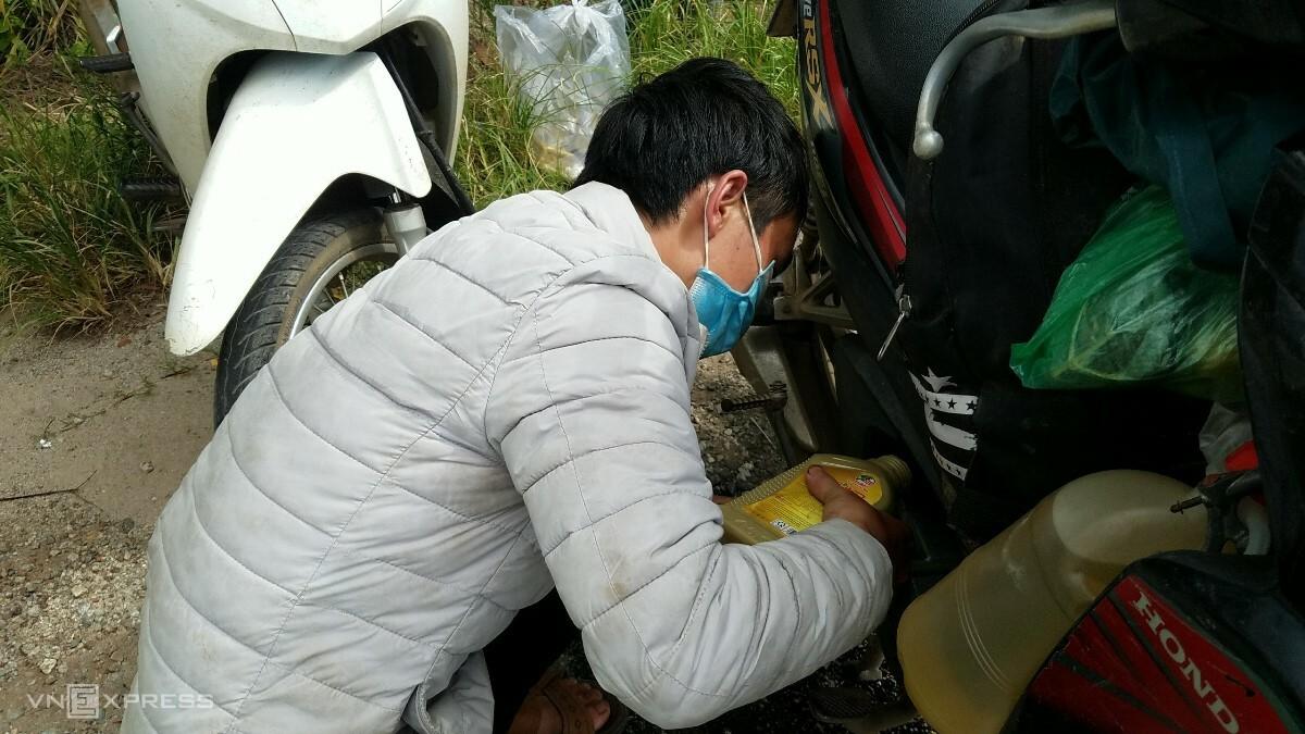 Anh Giàng Mi Hồ tranh thủ thay nhớt xe bên vệ đường. Ảnh: Võ Thạnh