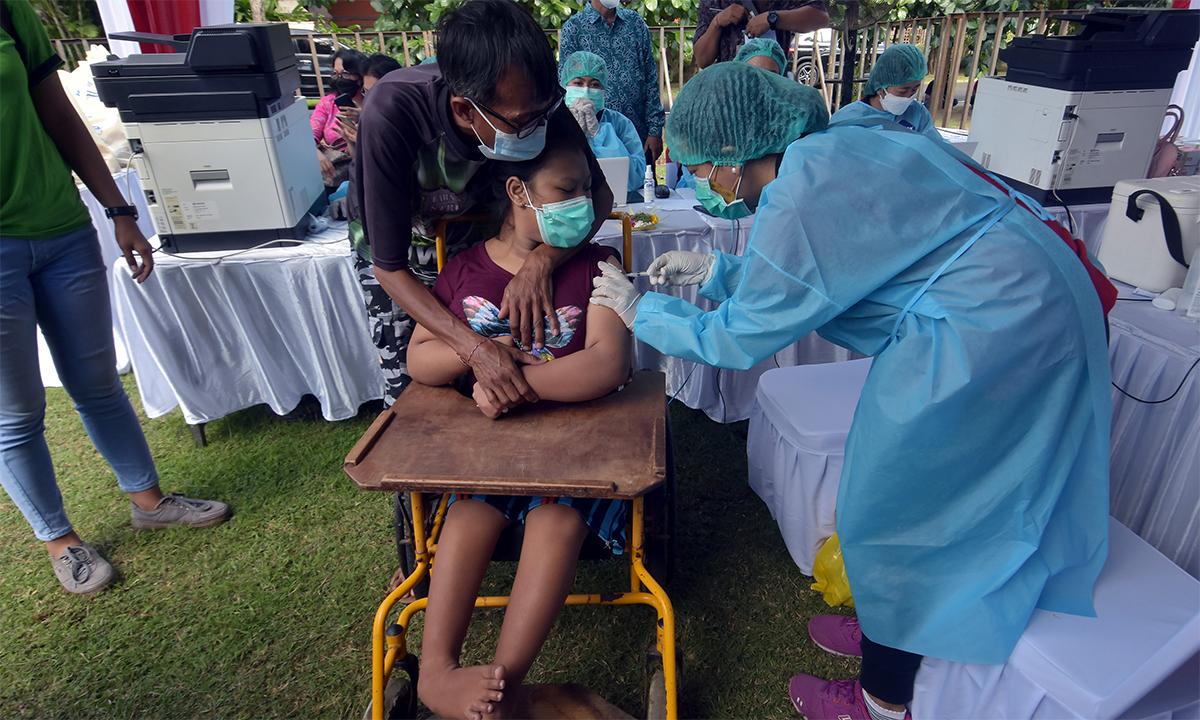 Nhân viên y tế Indonesia tiêm vaccien Covid-19 cho một phụ nữ khuyết tật trên đảo Bali ngày 7/9. Ảnh: Reuters.