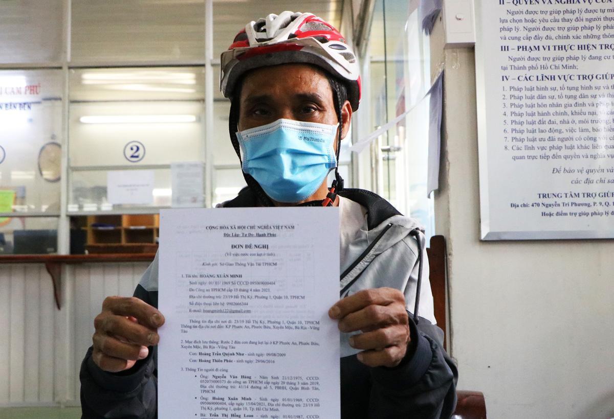 Ông Hoàng Xuân Minh hoàn tất thủ tục làm đơn đề nghị đón 2 con về lại TP HCM sau gần 4 tháng đi tránh dịch ở Bà Rịa - Vũng Tàu, sáng 5/10. Ảnh: Hà An