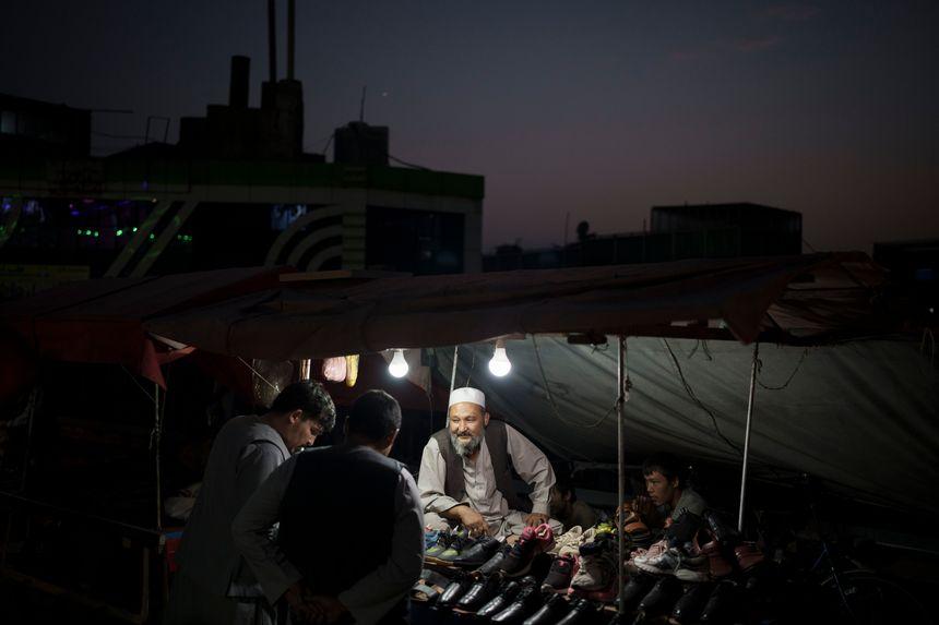 Một người bán hàng rong ở nói chuyện với khách tại khu chợ đường phố ở Kabul, Afghanistan tháng trước. Ảnh: AP.