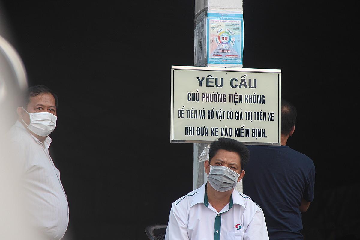 Anh Tuấn Thành (áo trắng, phải) ngồi đợi gần 6 giờ vẫn chưa thể đưa xe vào đăng kiểm.