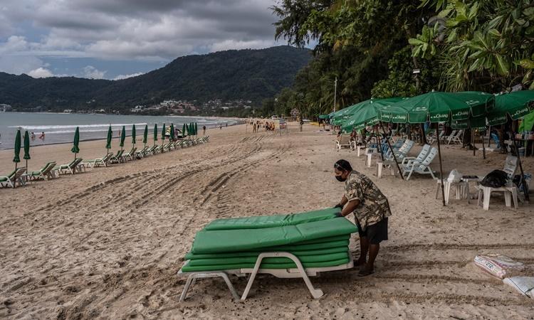 Một nhân viên đang thu dọn ghế tắm nắng ở Patong. Ảnh: NYTimes.