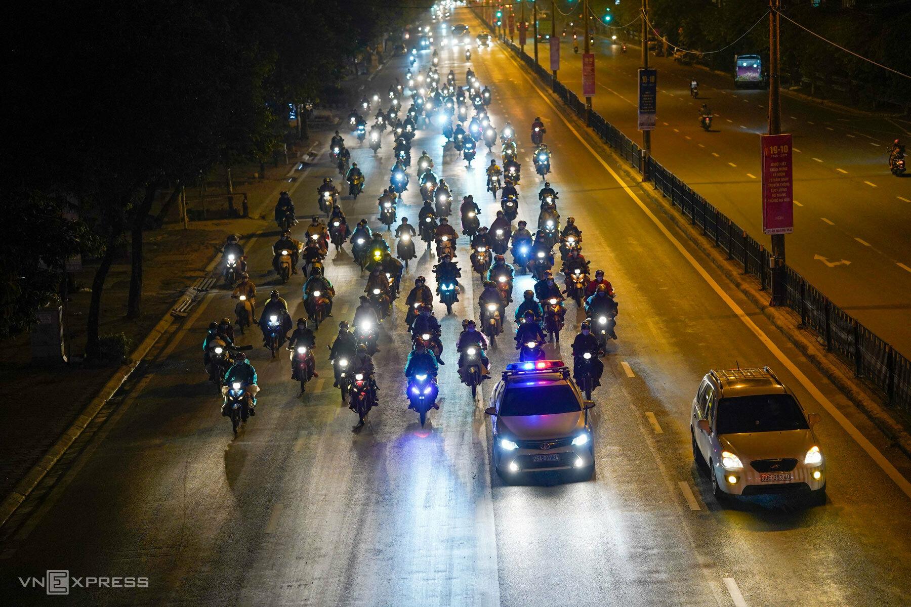 Cảnh sát giao thông Đội 8 dẫn đoàn người về quê đi xuyên thành phố Hà Nội, đêm 6/10. Ảnh: Phạm Chiểu