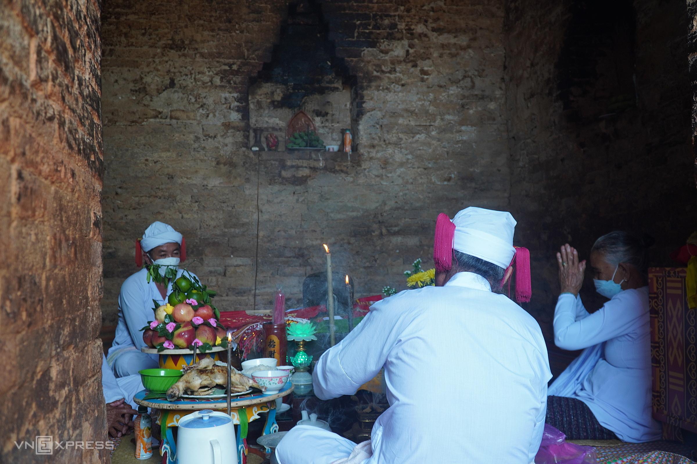 Sư cả Thông Minh Toàn (bên trái) đang hành lễ cùng thầy tế và bà Bóng trong tháp Pô Sha Inư. Ảnh: Việt Quốc