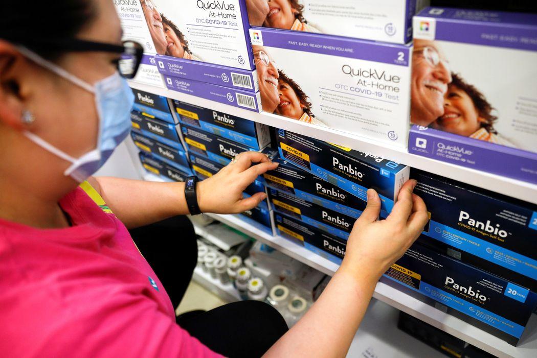 Nhân viên một hiệu thuốc ở Singapore sắp xếp các kit xét nghiệm nhanh Covid-19 trên kệ. Ảnh: Reuters.