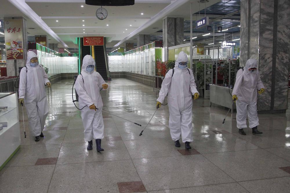 Nhân viên cửa hàng bách hóa số 1 Bình Nhưỡng khử trùng cửa hàng trước khi mở cửa hôm 28/12/2020. Ảnh: AP