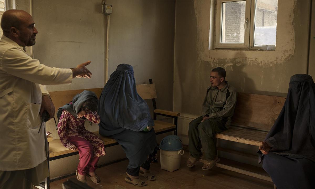 Bác sĩ Wahedullah Koshan (áo trăng) trò chuyện cùng người nghiện (thứ hai từ phải sang) và thân nhân của anh này tại  bệnh viện Avicenna ở Kabul ngày 4/10. Ảnh: AP.