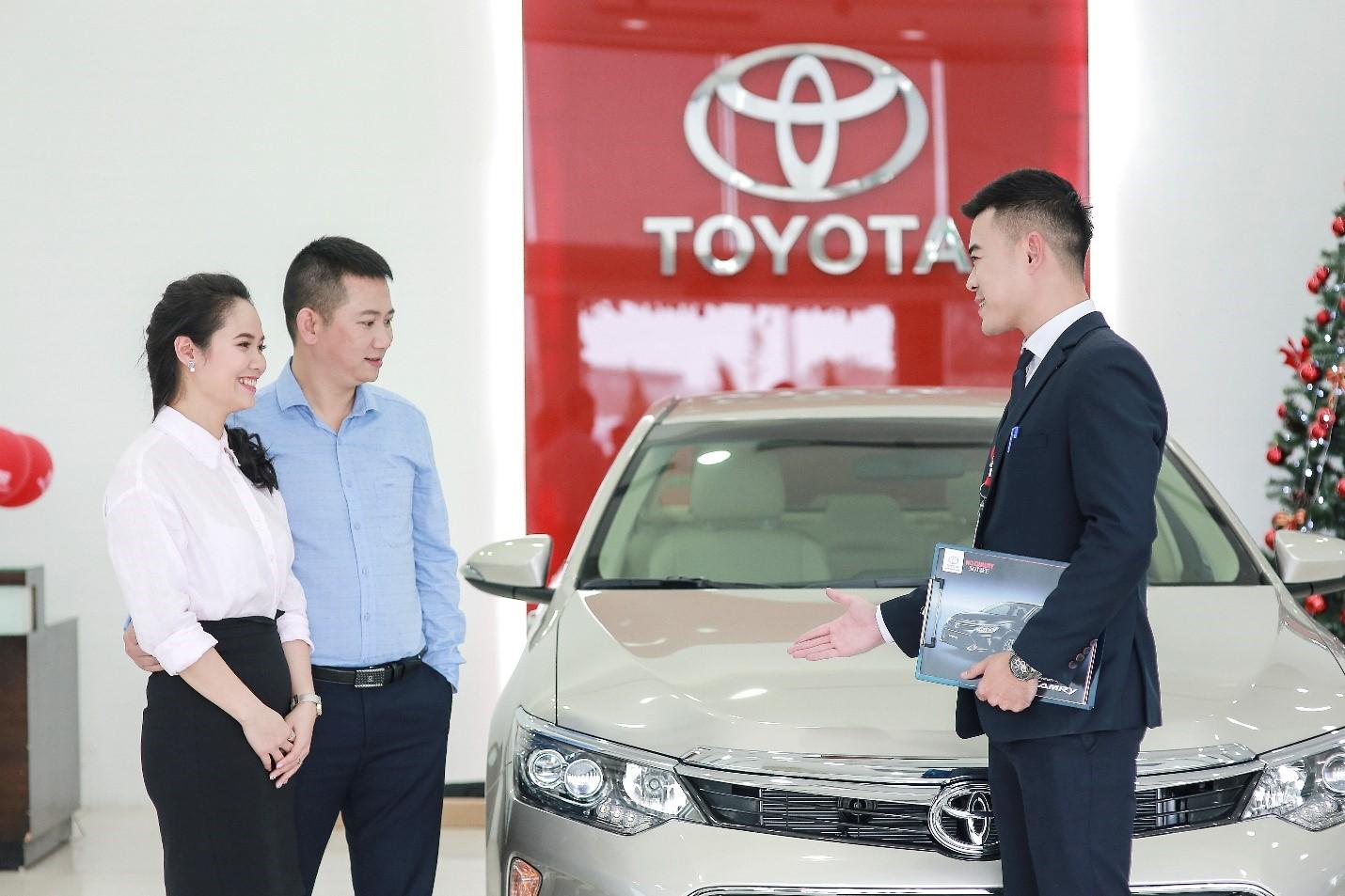 Nhân viên đại lý Toyota (áo đen) tư vấn xe cho khách hàng.