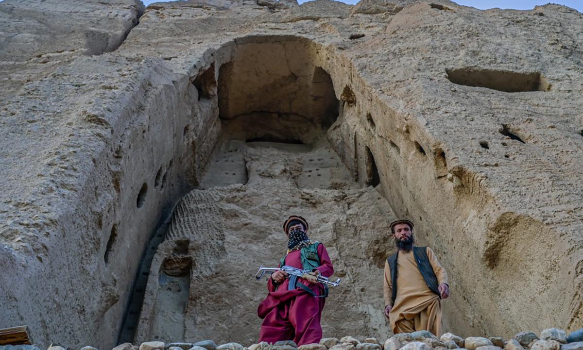 Hai thành viên Taliban đứng gác ở khu phế tích tượng Phật khổng lồ tại tỉnh  Bamiyan, Afghanistan. Ảnh: AFP.