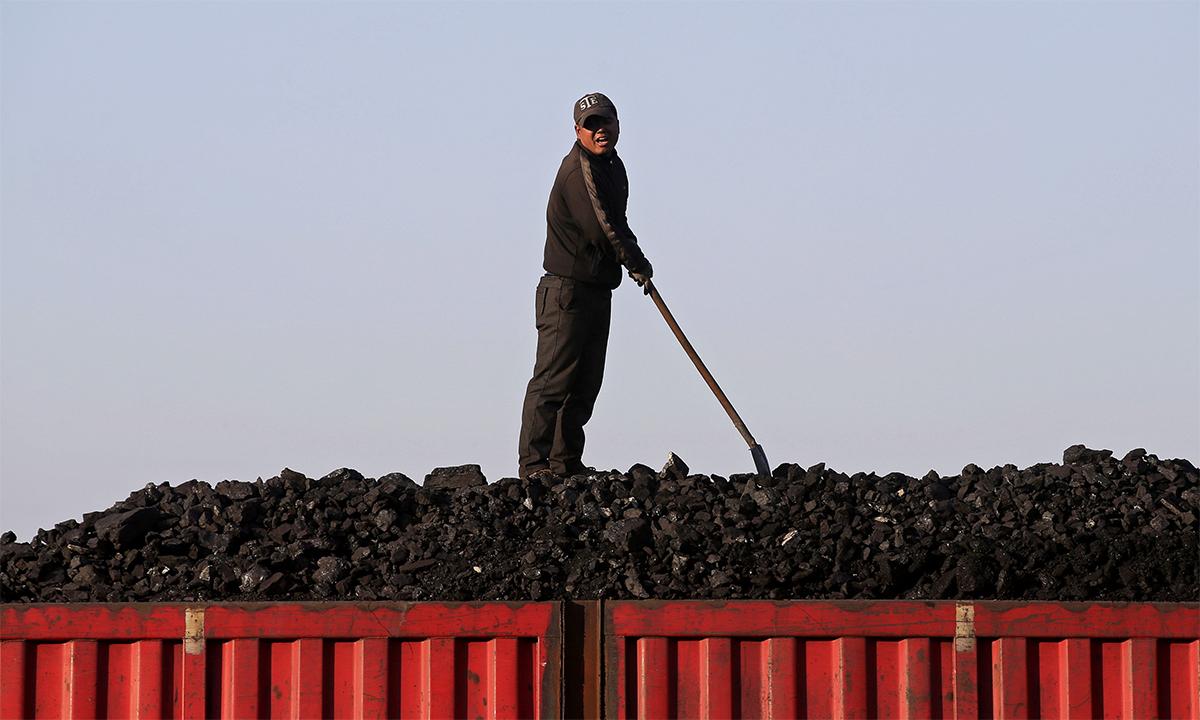 Công nhân Trung Quốc đứng trên đống than chờ bốc lên xe tải tại một mỏ khai thác ở tỉnh Hắc Long Giang tháng 10/2015. Ảnh: Reuters.