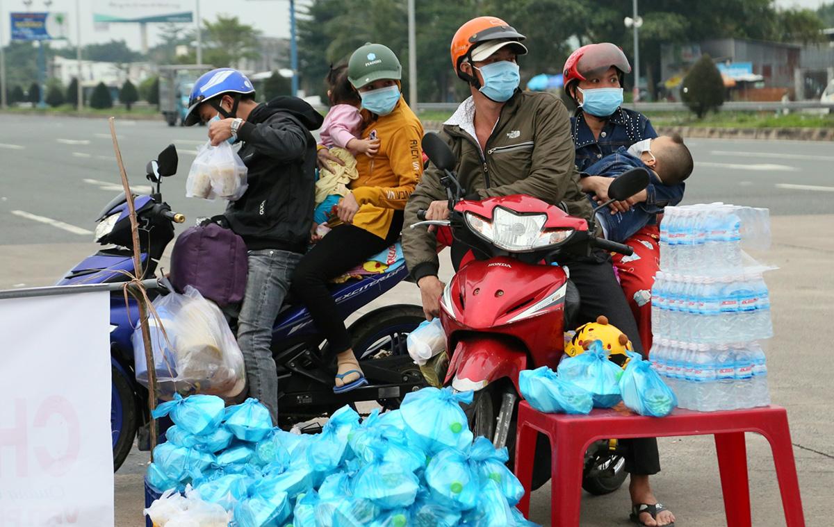 Một điểm cung cấp thức ăn, nước uống miễn phí cho người dân về quê trên đường dẫn cầu Cần Thơ. Ảnh: Cửu Long
