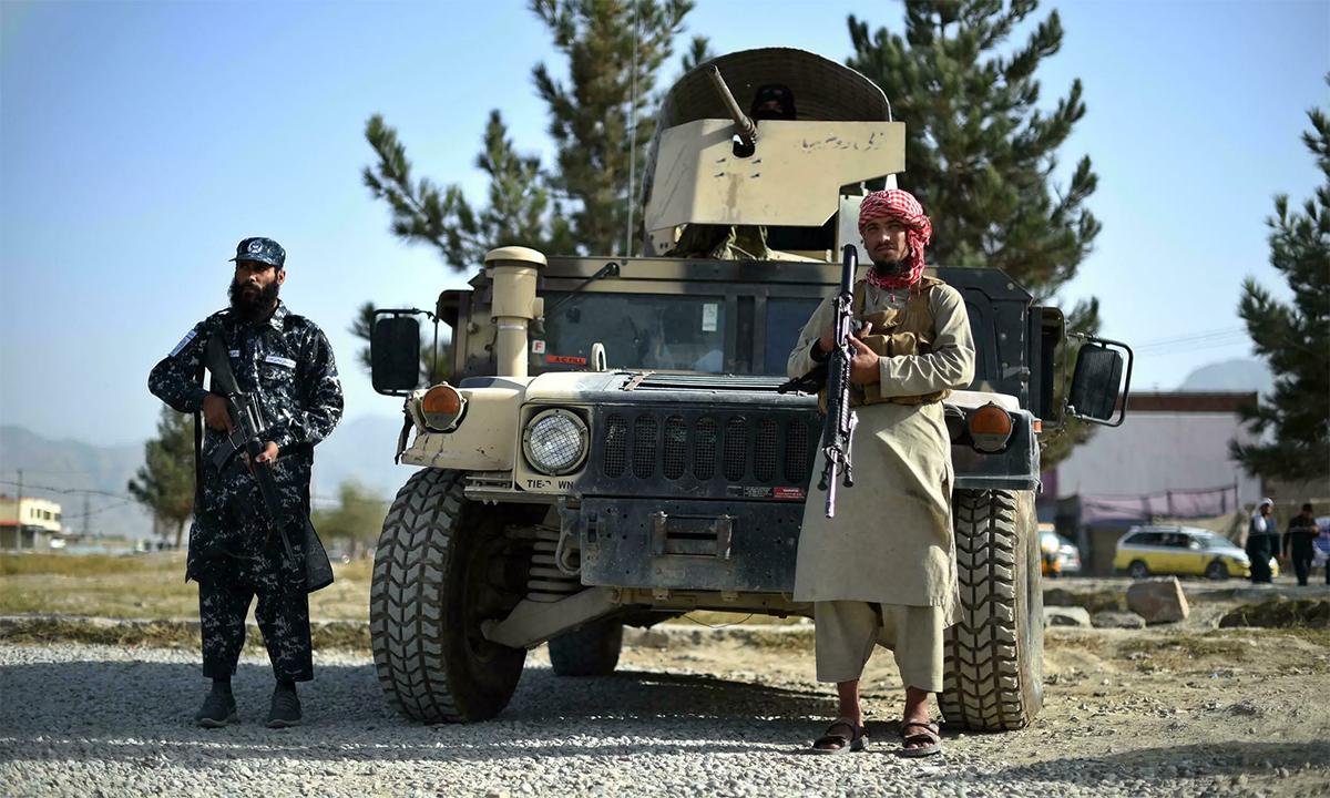 Lính Taliban đứng gác cạnh một xe Humvee tại cổng một sở cảnh sát quận ở thủ đô Kabul, Afghanistan ngày 3/10. Ảnh: AFP.