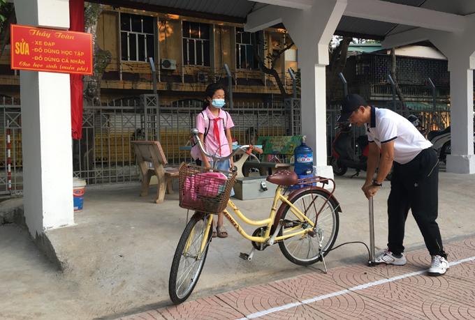 Thầy Toàn giúp học sinh bơm xe tại quán trong trường Tiểu học Kim Đồng, thành phố Lào Cai. Ảnh: Nhân vật cung cấp