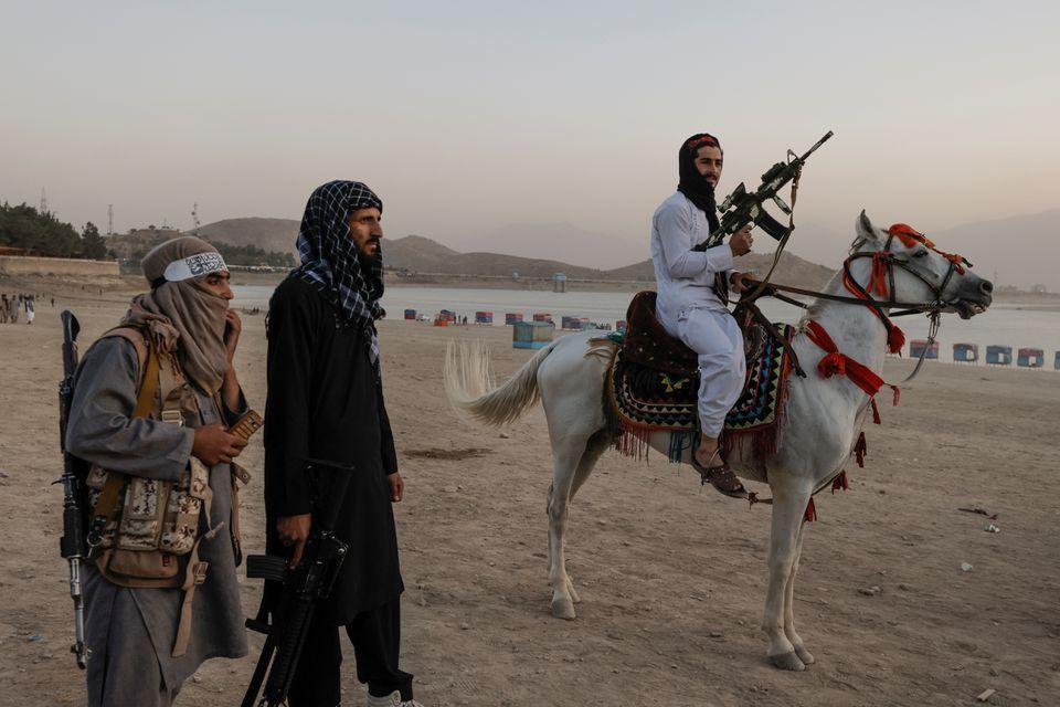 Chiến binh Taliban ôm súng cưỡi ngựa tại công viên giải trí bên hồ Qargha ở Kabul, Afghanistan, hôm 9/10. Ảnh: Reuters.