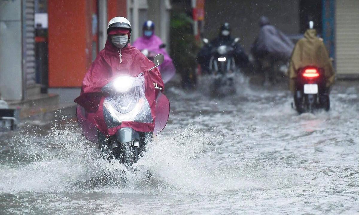 Xe máy di chuyển khó khăn qua đường ngập nước ở Khương Hạ, Khương Đình, Hà Nội, sáng 11/10. Ảnh: Ngọc Thành