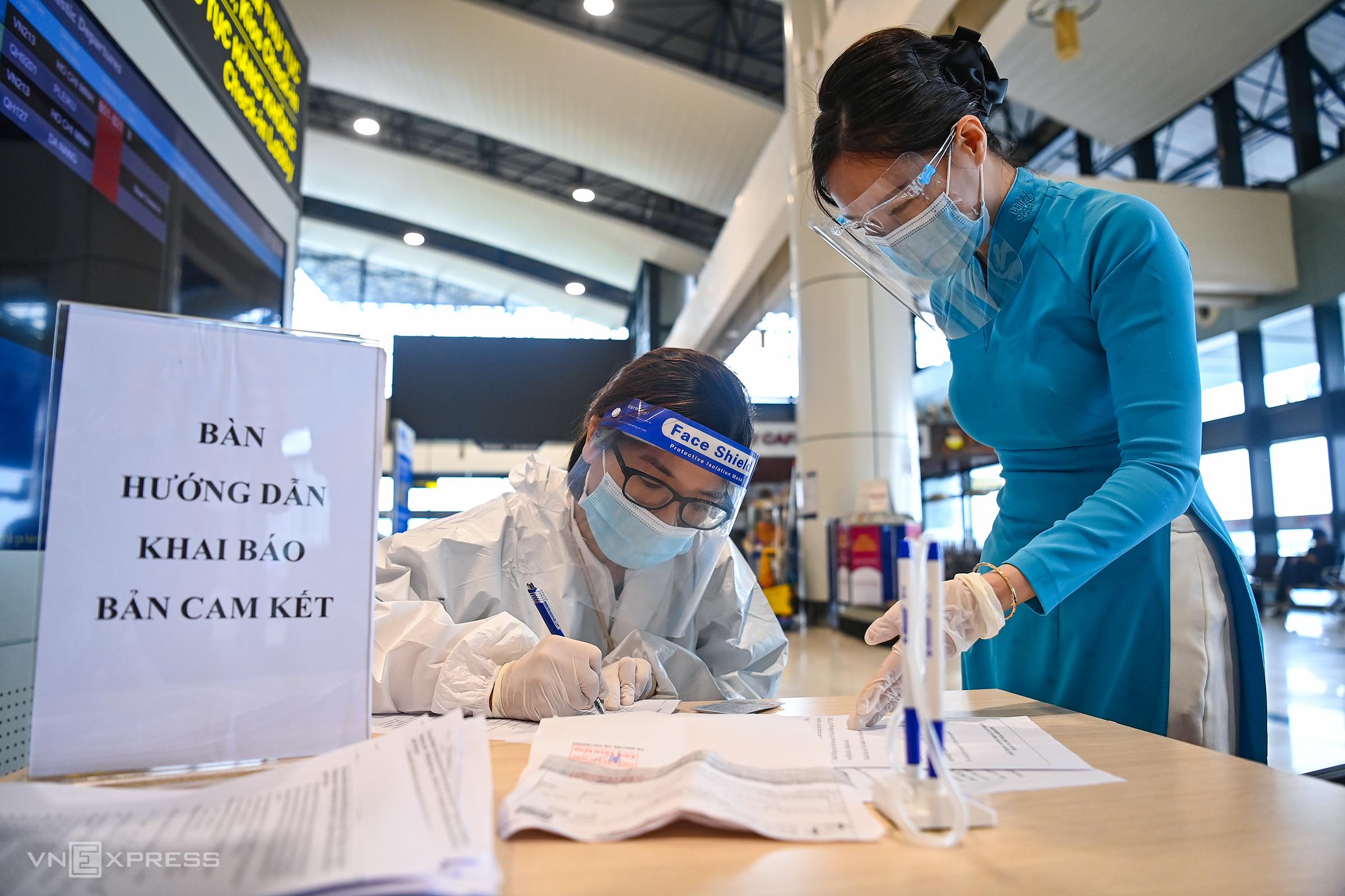 Tiếp viên hành không hướng dẫn hành khách khai báo y tế tại sân bay Nội Bài, ngày 10/10. Ảnh: Giang Huy