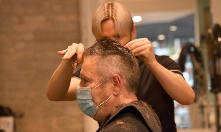 Một khách hàng trong tiệm cắt tóc được hoạt động trở lại ở Sydney, bang New South Wales, Australia, ngày 11/10. Ảnh: AFP.