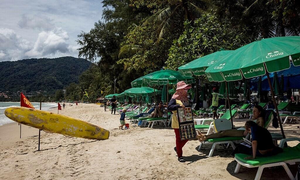 Người bán hàng và du khách trên bãi biển ở Phuket, Thái Lan, hồi tháng 8. Ảnh: AFP.