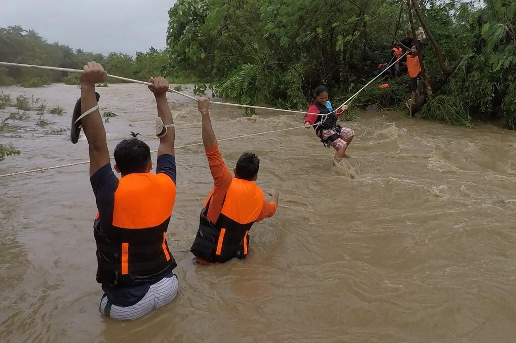 Nhân viên cứu hộ sơ tán người dân khỏi căn nhà gần con sông nước dâng cao do mưa lớn từ bão Kompasu ở thị trấn Gonzaga, tỉnh Cagayan, phía bắc Manila hôm 11/10. Ảnh: AFP.