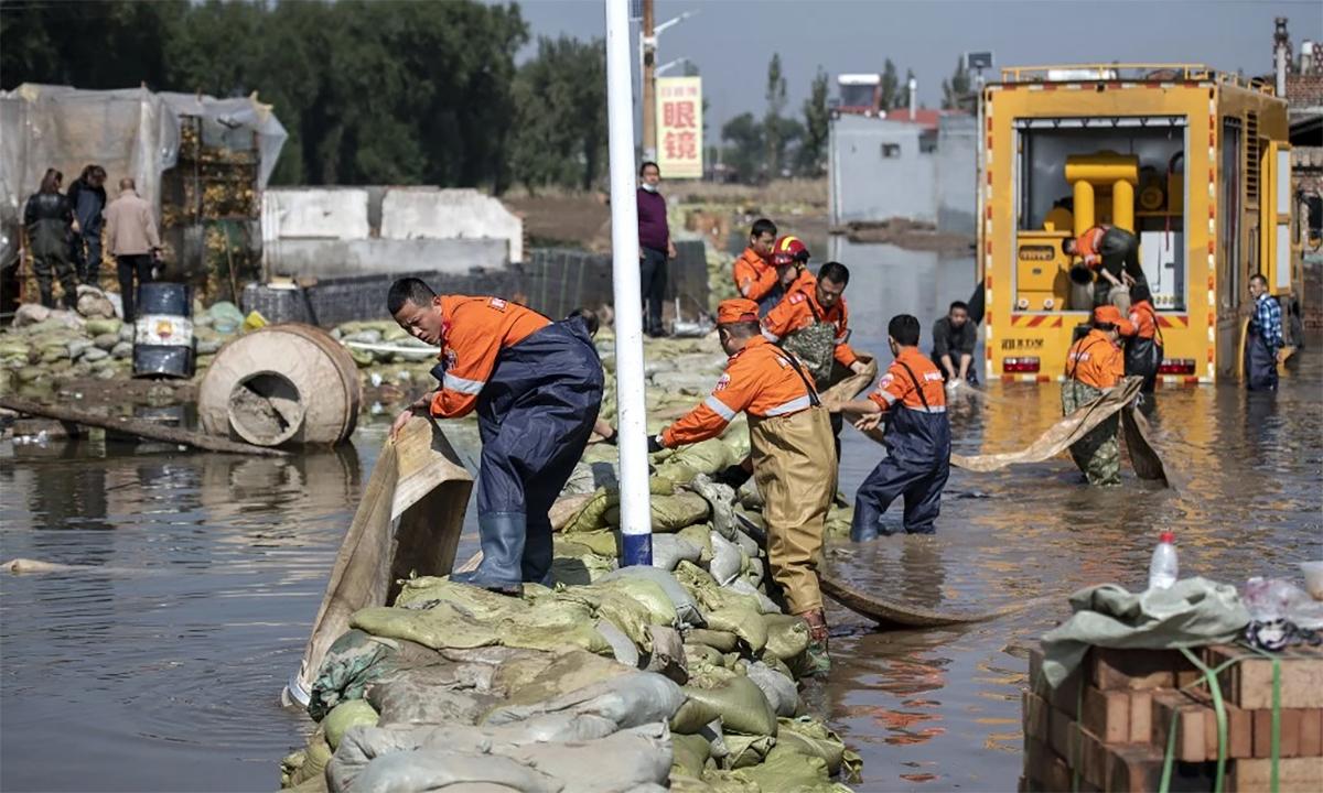 Nhân viên cứu hộ Trung Quốc bơm nước ra khỏi một khu vực bị ngập ở thành phố Tấn Trung, tỉnh Sơn Tây ngày 11/10. Ảnh: AFP.
