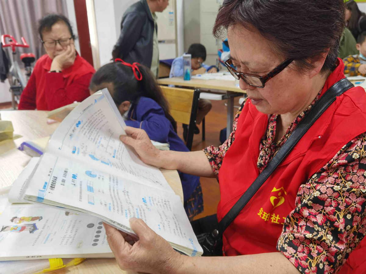 Một thành viên của đội bà ngoại chia sẻ đang giám sát trẻ làm bài tập về nhà hồi tháng 5. Ảnh: China Daily