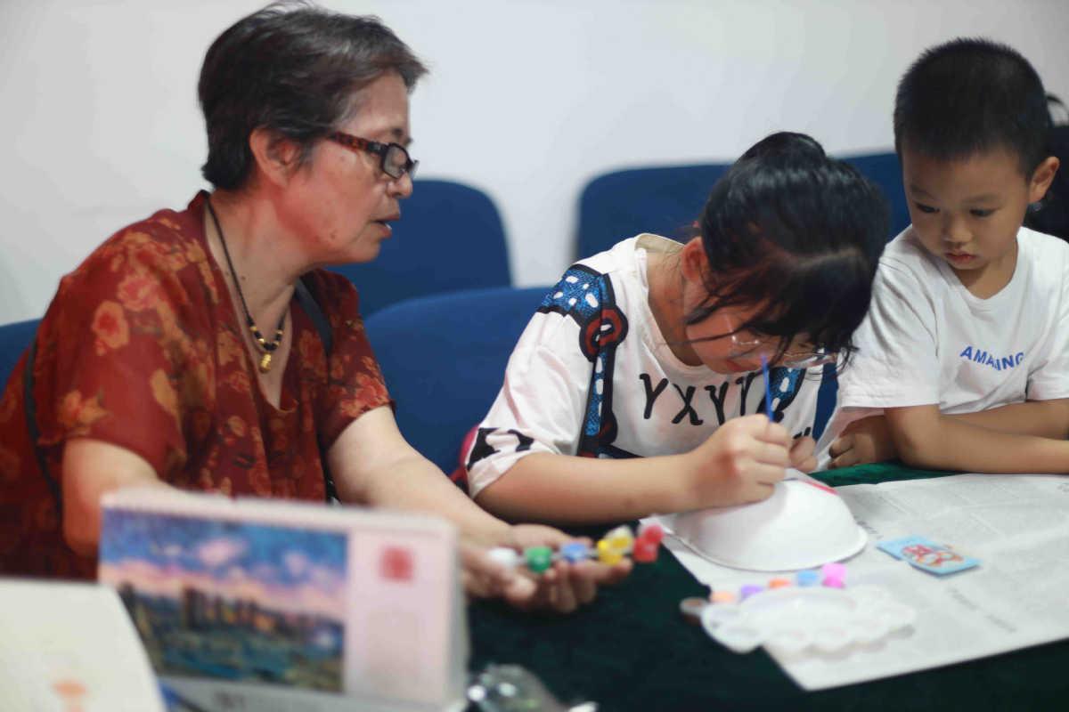 Một bà ngoại chia sẻ giúp học sinh vẽ mặt nạ trong một giờ học miễn phí về kinh kịch ở quận Cửu Long Pha, thành phố Trùng Khánh, hồi tháng 7. Ảnh: China Daily