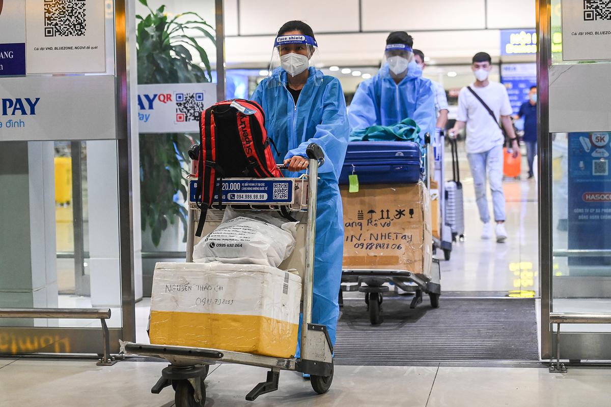 Hành khách rời nhà ga Nội Bài tối 11/10. Đây là những hành khách bay thương mại đầu tiên từ TP HCM đến Hà Nội sau khi hành không khôi phục chuyến bay nội địa. Ảnh: Giang Huy.