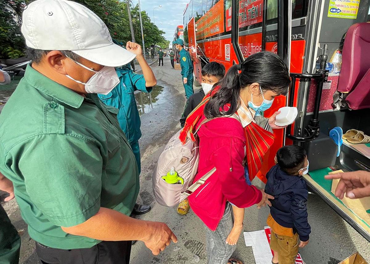 Người phụ nữ bế con nhỏ đi bộ từ Long An về TP HCM được quân đội đưa về quê. Ảnh: Lê Hiếu