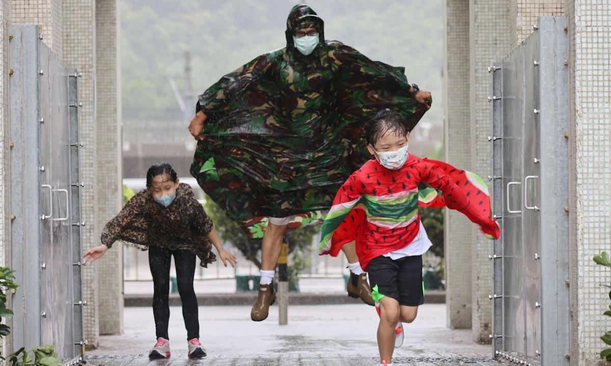 Một gia đình chạy trong mưa ở Chai Wan, Hong Kong hôm nay. Ảnh: SCMP.
