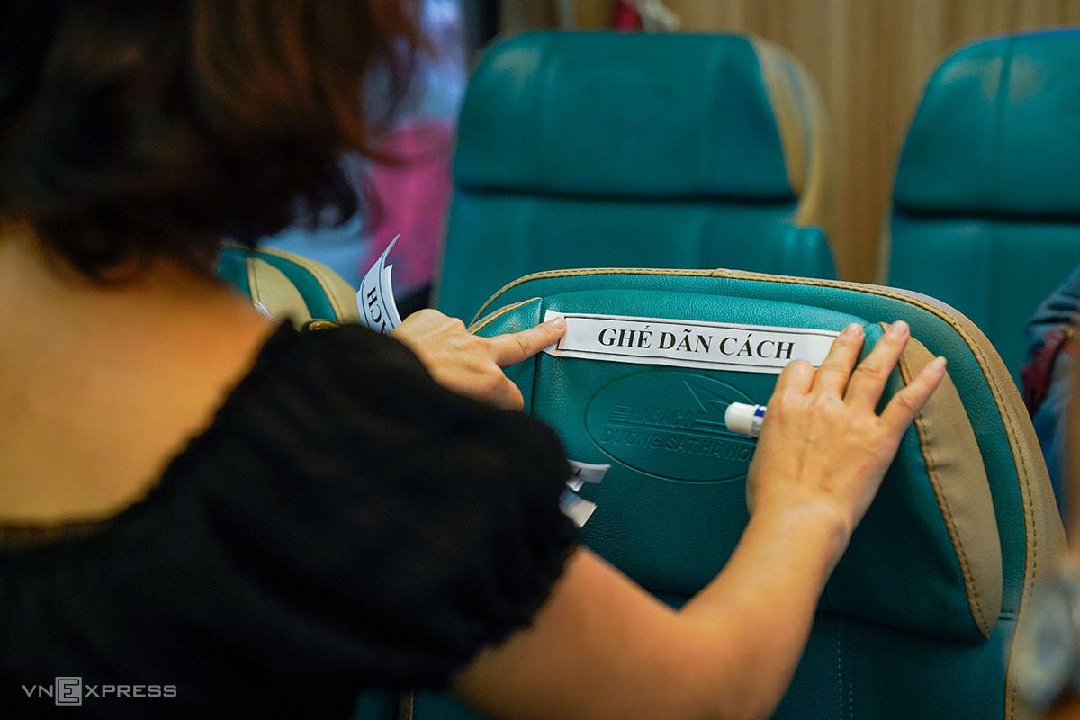 Nhân viên tàu dán biển đánh dấu ghế để hành khách ngồi giãn cách. Ảnh: Phạm Chiểu.