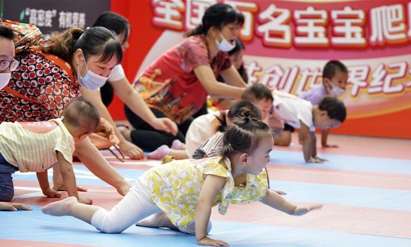 Phụ huynh và con trẻ tham gia cuộc thi bò trẻ em tại một trung tâm mua sắm ở Bắc Kinh, Trung Quốc, ngày 13/9/2020. Ảnh: Xinhua