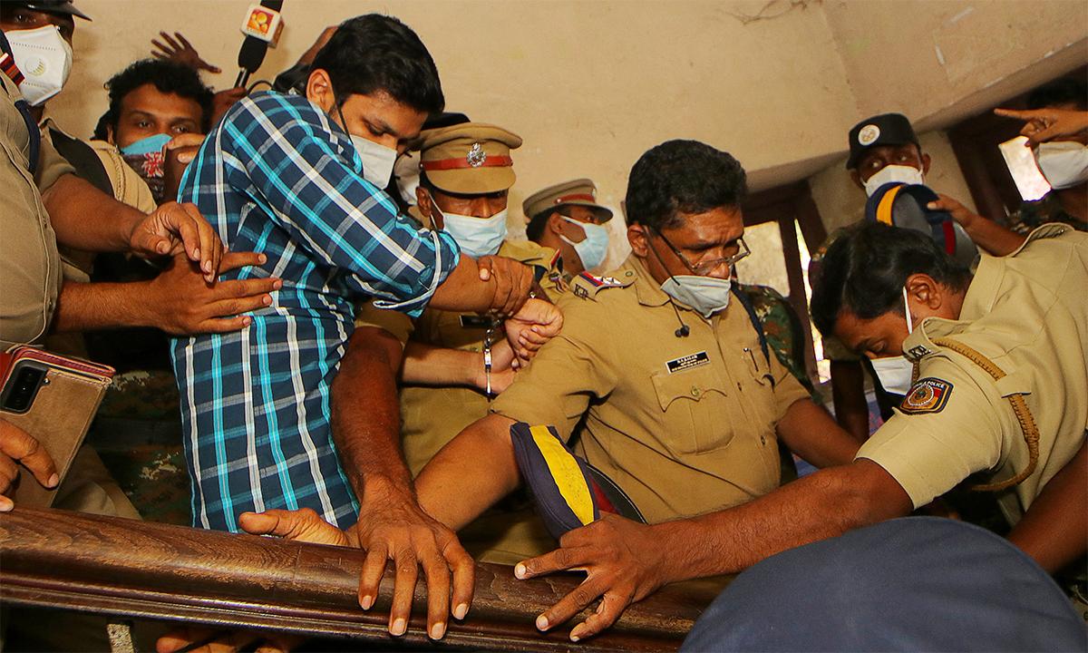 Cảnh sát áp giải Sooraj Kumar (áo kẻ xanh) ra khỏi tòa án tại quận Kollam ngày 13/10. Ảnh: AFP.