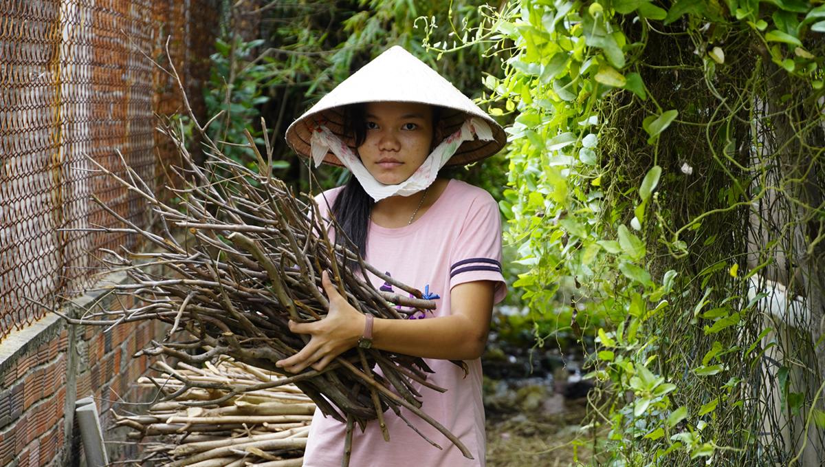 Nguyễn Thị Phương Quyên ra trước nhà nhặt củi giúp bà ngoại. Ảnh: Hoàng Nam