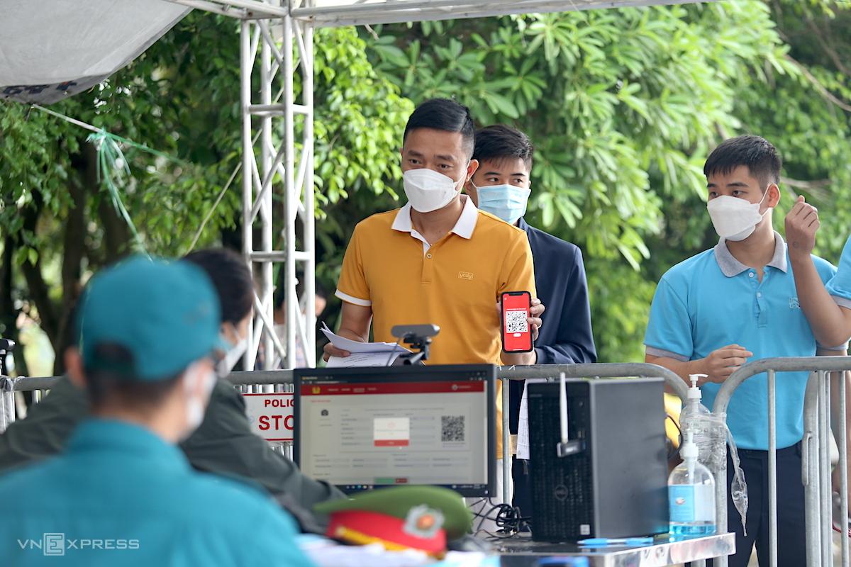 Người dân khai báo y tế tại chốt giáp ranh Hà Nội - Bắc Ninh, sáng 14/10. Ảnh: Gia Chính