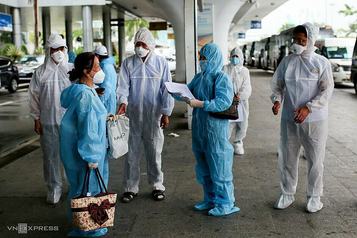 Nhân viên y tế lấy thông tin người về trên chuyến bay giải cứu từ TP HCM về Đà Nẵng, trưa 12/10. Ảnh: Nguyễn Đông